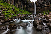 Blurred view of waterfall over rocky creek, Skaftafell, Iceland, Iceland