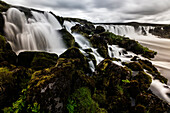 Waterfall pouring over rock formations in remote river, Southern Highlands, Iceland, Iceland