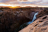 Waterfall flowing over rocky cliffs in remote landscape, Augrabies, Northern Cape, South Africa