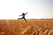 Caucasian woman jumping for joy in rural field, Nizhniy Tagil, Sverdlovsk region, Russia