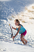 Caucasian girl climbing sand dune with sled, White Sands, New Mexico, USA