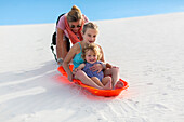 Caucasian mother and children sledding on sand dune, White Sands, New Mexico, USA
