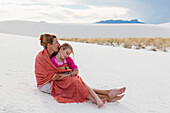 Caucasian mother and daughter wrapped in blanket on sand dune, White Sands, New Mexico, USA