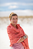 Caucasian woman smiling on sand dune, White Sands, New Mexico, USA