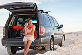 Caucasian woman leaning on car drinking coffee, White Sands, New Mexico, USA