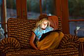 Caucasian girl using digital tablet in armchair at night, Santa Fe, New Mexico, USA