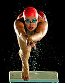 Mixed race swimmer diving off starting block, Bainbridge island, WA, USA