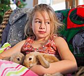 Caucasian girl holding pet rabbits on sofa, Santa Fe, New Mexico, USA