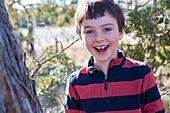 Close up of Caucasian boy smiling near tree, Santa Fe, New Mexico, USA