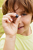 Caucasian boy holding blueberry outdoors, Los Angeles, CA, USA