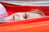 Close up of Caucasian girl peeking over hammock, Hope, Idaho, USA
