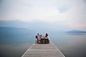 Caucasian family at picnic table on wooden dock over lake, Hope, Idaho, USA