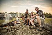 Three generations of Caucasian men roasting hot dogs over campfire, Saint Louis, Missouri, USA