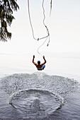 Man jumping from rope swing into lake, Hope, Idaho, USA