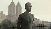 Caucasian runner listening to earbuds in front of city skyline, New York, New York, USA