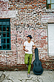 Mixed race musician with guitar case using cell phone, Los Angeles, California, USA