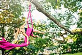 Acrobatic Caucasian girl hanging on fabric under tree, C1