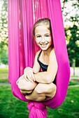 Acrobatic Caucasian girl sitting in hanging fabric, C1