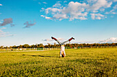Caucasian girl doing headstand in field on ranch, C1