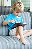 Caucasian boy using digital tablet on sofa, C1
