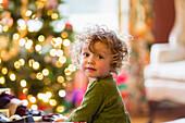 Caucasian baby boy sitting near Christmas tree, C1