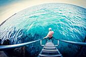 Fish-eye lens view of older Caucasian man descending ladder into ocean, C1