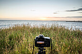 Close up of camera photographing sunset over ocean horizon, C1