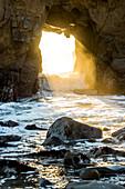 Sunbeam shining through rock formation to ocean waves, Big Sur, California, United States