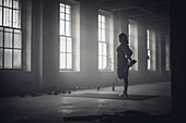 Black woman stretching in dark gym, Saint Louis, MO, USA