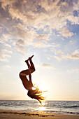 Silhouette of mixed race woman doing backflip on beach, The Big Island, Hawaii, United States
