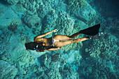 Mixed race woman snorkeling near tropical reef, The Big Island, Hawaii, United States