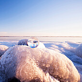 Glass sphere on frozen rock formations, kingston, ontario, canada