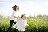 2 young girls running in the country in spring