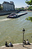 France, Paris, end of Ile St Louis, young couples, boat on the Seine