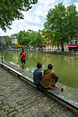 France, Paris, Jogger woman and a couple sitting on the edge of Canal St Martin