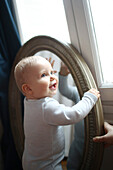 A 10 months baby boy in front of a mirror