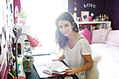A teenage girl doing her homework in her room