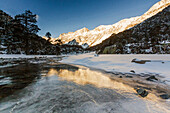 France, Midi Pyrenees, Hautes Pyrenees, First light of day on the summits of Marcadau valley reflected in the frozen river
