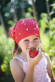 Girl picking fresh vegetables in a garden
