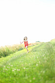 A 7 years girl running with poppies in the hand, on a country lane