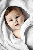 Portrait of a 4 months old baby naked in a towel