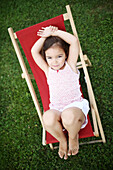 Portait of a 4 years old girl on a lounge chair for child