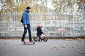 A 3 years old little boy on bike going with his father on skateboarding, in the streets of Paris