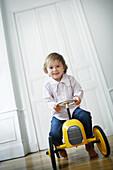 Little boy on a yellow toy car