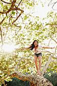 Hispanic woman standing on tree branch