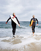 Two men walking into ocean with surfboards