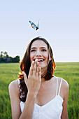 Woman watching butterfly in meadow