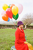 Mixed race woman holding colorful bunch of balloons