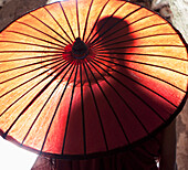 Silhouette of Asian man behind sun umbrella