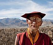 Elderly Tibetan monk in eyeglasses and hat